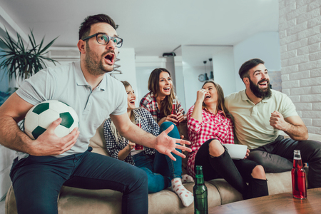 Photo pour Happy friends or football fans watching soccer on tv and celebrating victory at home.Friendship, sports and entertainment concept. - image libre de droit