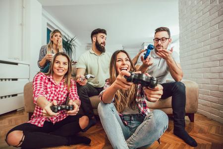 Foto de Group of friends play video games together at home, having fun. - Imagen libre de derechos