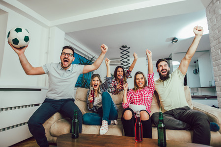 Foto de Happy friends or football fans watching soccer on tv and celebrating victory at home.Friendship, sports and entertainment concept. - Imagen libre de derechos