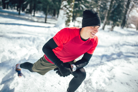 Photo for Young man in sporty wear alone doing exercise before running at white snow covered place - Royalty Free Image
