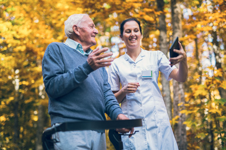 Photo pour Smiling caregiver nurse and disabled senior patient in walker using digital tablet outdoor - image libre de droit