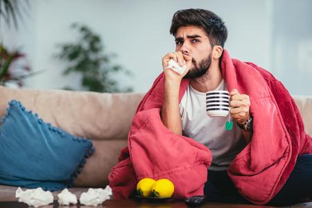Foto de Young ill man drinking hot tea at home and watching tv - Imagen libre de derechos