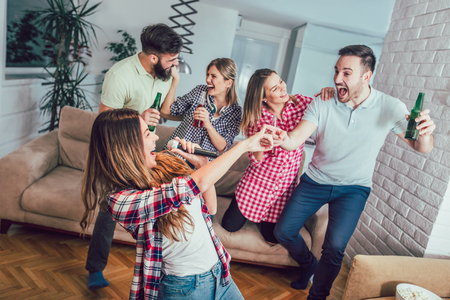 Photo for Group of friends playing karaoke at home. Concept about friendship, home entertainment and people - Royalty Free Image