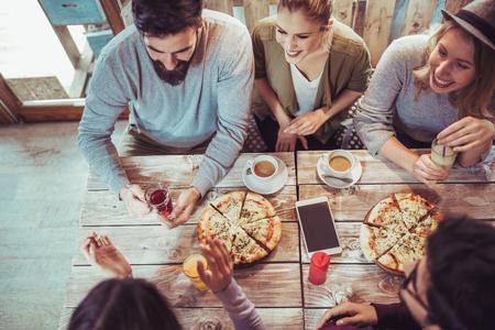 Foto de Young friends sharing pizza in a indoor cafe top view - Imagen libre de derechos