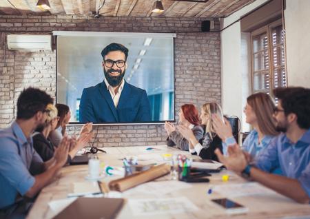 Foto de Business people looking at projector during video conference in office - Imagen libre de derechos