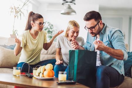 Foto de Two women and a man in a living room holding a credit card and shopping bags - Imagen libre de derechos
