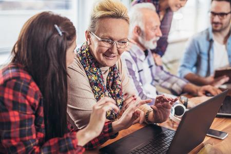 Foto de Young volunteers help senior people on the computer. Young people giving senior people introduction to internet - Imagen libre de derechos