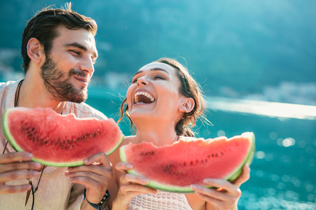 Photo for Cheerful couple holding slices of watermelon - Royalty Free Image