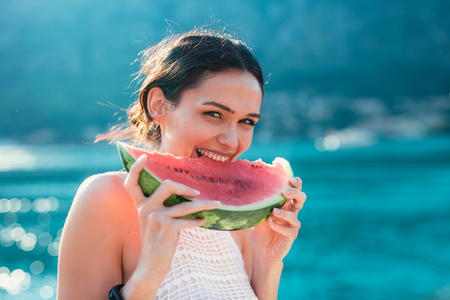 Photo pour Attractive young woman on the beach eating watermelon - image libre de droit