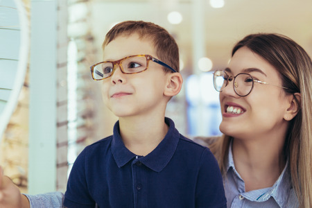 Foto de Mother with son choosing glasses in optics store. - Imagen libre de derechos