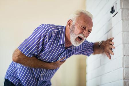 Foto de Senior man suffering from heart attack at home - Imagen libre de derechos