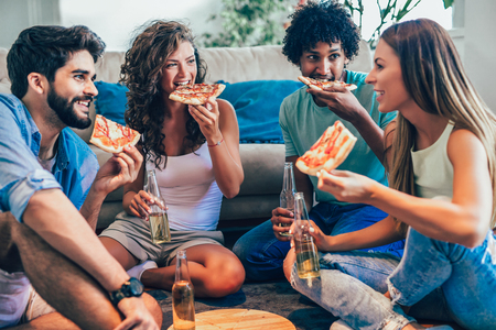 Foto de Group of young friends eating pizza.Home party. - Imagen libre de derechos