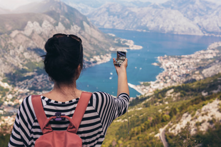 Photo for Tourist hold compass on trip, lifestyle concept adventure, traveler with backpack on background mountain and blue sea landscape horizon. View of the Bay of Kotor from the mountains Lovcen. - Royalty Free Image