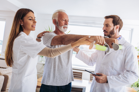 Photo pour Man having chiropractic arm adjustment. Physiotherapy, sport injury rehabilitation. Senior man exercises in center for chiropractic. - image libre de droit