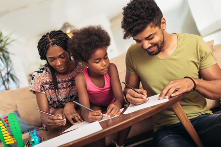 Foto de Mom and dad drawing with their daughter. African american family spending time together at home. - Imagen libre de derechos