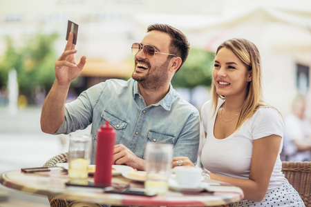 Photo pour Pay the bill. Attractive young couple holding credit card while siting in sidewalk cafe. - image libre de droit