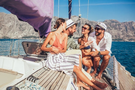 Photo pour Smiling friends sitting on sailboat deck and having fun.Vacation, travel, sea, friendship and people concept - image libre de droit
