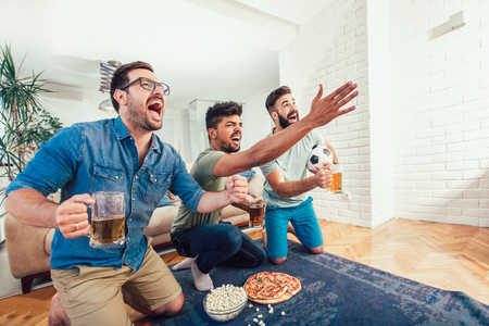 Photo pour Happy male friends watching sports on tv and drinking beer. - image libre de droit