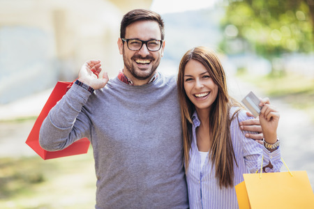Photo pour Portrait of happy couple with shopping bags after shopping in city smiling and holding credit card - image libre de droit