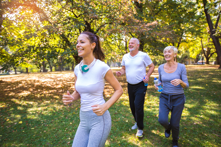 Photo pour Senior man and woman and young female instructor  workout on fresh air. Outdoor activities, healthy lifestyle, strong bodies, fit figures. Stylish, modern sportswear. Different generations - image libre de droit