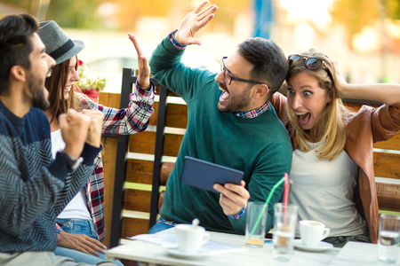 Photo pour Group of four friends having a coffee together. Two women and two men at cafe talking laughing and enjoying their time using digital tablet. - image libre de droit