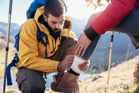 Foto für A woman has sprained her ankle while hiking, her friend uses the first aid kit to tend to the injury - Lizenzfreies Bild