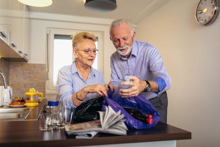 Foto de Senior couple separating recyclable trash at home - Imagen libre de derechos