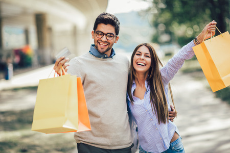 Foto de Portrait of happy couple with shopping bags after shopping in city smiling and holding credit card - Imagen libre de derechos