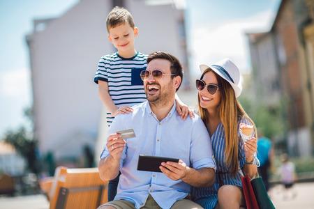 Foto de Smiling parents and little boy with tablet pc and credit card outdoor - Imagen libre de derechos