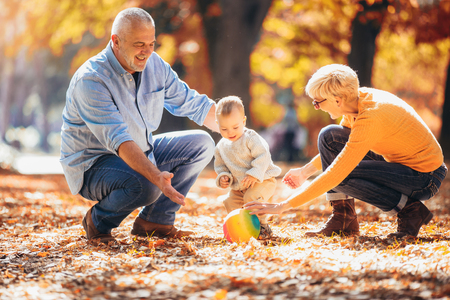Foto de Grandparents and grandson together in autumn park - Imagen libre de derechos