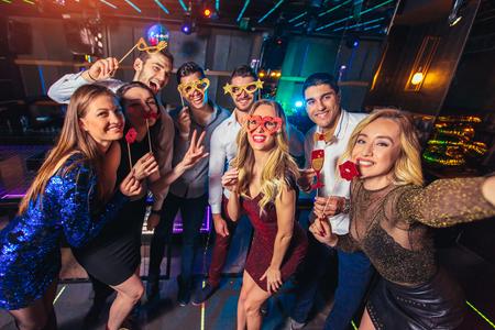 Photo pour Group of friends partying in a nightclub make selfie photo - image libre de droit