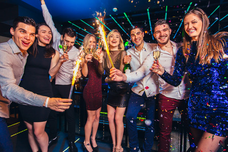 Photo pour Group of friends partying in a nightclub and toasting drinks. - image libre de droit