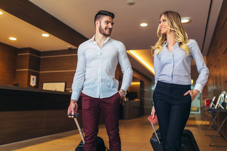 Photo for Young couple near reception desk in hotel. Young couple leaving hotel - Royalty Free Image