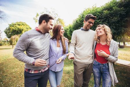 Photo pour Group of young people walking through park. Friends having fun outdoor - image libre de droit