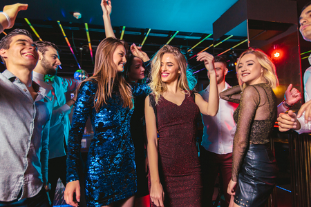 Photo for Young happy people are dancing in club. Nightlife and disco concept. - Royalty Free Image