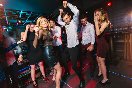 Photo pour Young happy people are dancing in club. Nightlife and disco concept. - image libre de droit