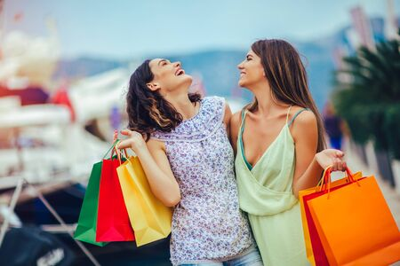 Photo for Female friends with shopping bags walking by the harbor of a touristic sea resort with boats on background - Royalty Free Image