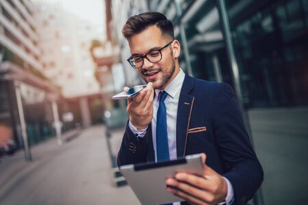 Photo for Young business man using voice command recorder on smartphone. - Royalty Free Image
