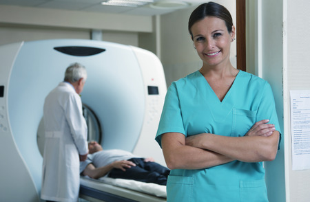 Happy young female doctor with man patient in background undergoing CT scan.