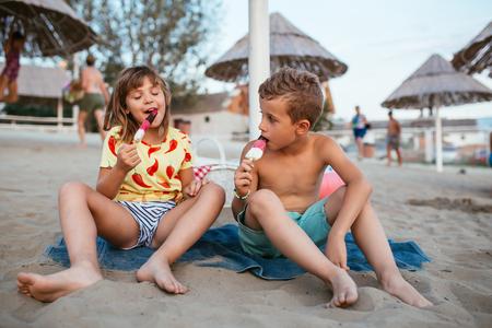 Foto de Happy positive children sitting on the sandy beach and eating ice cream. People, children, friends and friendship concept - Imagen libre de derechos