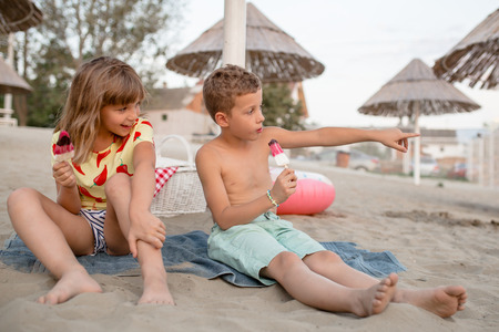 Photo for Happy positive children sitting on the sandy beach and eating ice cream. People, children, friends and friendship concept - Royalty Free Image