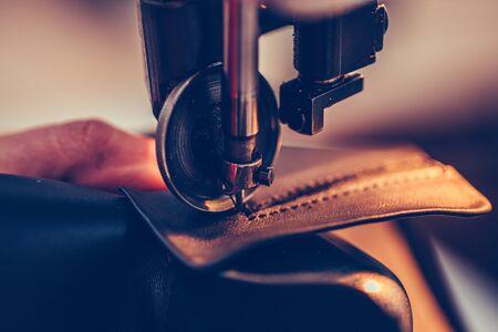 Foto de Female shoemaker hands stitching a part of the shoe  in the handmade footwear industry - Imagen libre de derechos