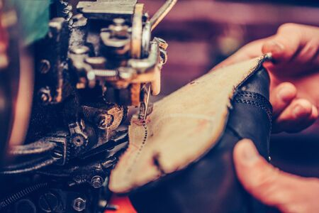 Photo pour Hands of an experienced shoemaker stitching a part of the shoe in a shoe factory - image libre de droit