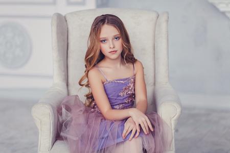 Photo pour portrait of beautiful caucasian little girl wearing dress, sitting on chair - image libre de droit