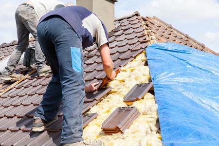 Photo pour a roofer laying tile on the roof - image libre de droit