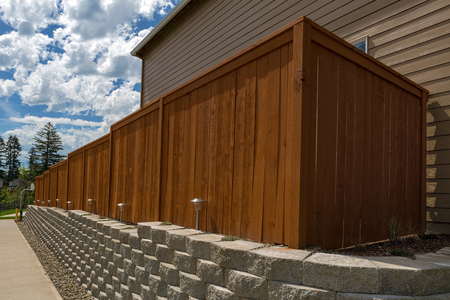 Photo pour Wood fence cement stack stone blocks retaining wall and landscaping lighting - image libre de droit