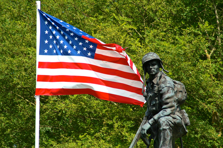 Photo for Bronze statue of an Iron Mike, a soldier of the American Army holding a gun with a flag of the United States of America. La Fiere Bridge, Sainte-Mere-Eglise, Normandy, France - Royalty Free Image