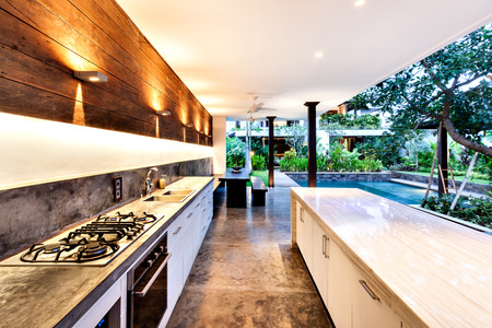 Photo pour Outdoor kitchen with a stove an countertop next to garden including a pool in luxury hotel or house - image libre de droit