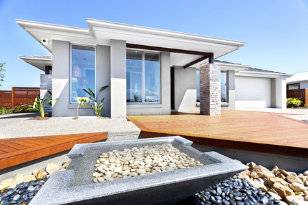 Photo pour Well decorated yard and garden using stone elements in front of a modern house, closeup of a small square shape pond made by pure stone included gravel and water inside of it. There are white and black rocks around the pond. - image libre de droit