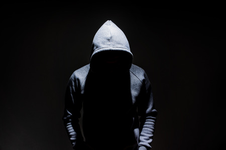 Photo for Silhouette of man in the hood, dark mysterious man hoodie, murderer, hacker, anonymus on the black background with free space - Royalty Free Image